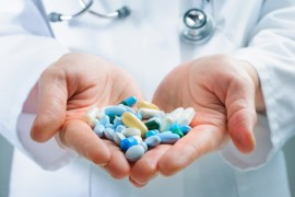 Hand of doctors holding many different pills