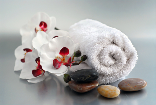 White rolled up towel with massage stones and an orchid