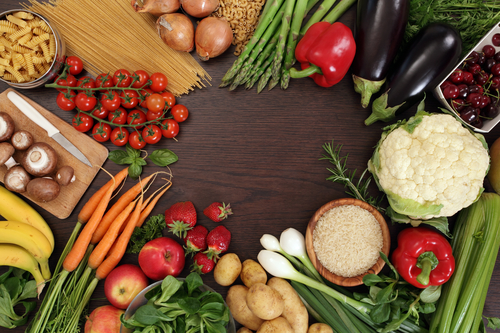 Photo of a table top full of fresh vegetables, fruit, and other healthy foods with a space in the middle for text.